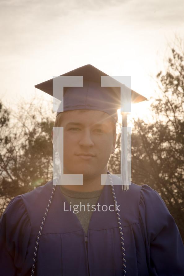 graduate standing in bright sunlight