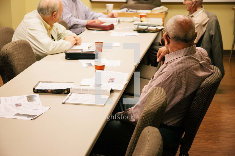 elderly men at a table at a Bible study