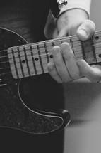 Hand holding guitar neck.