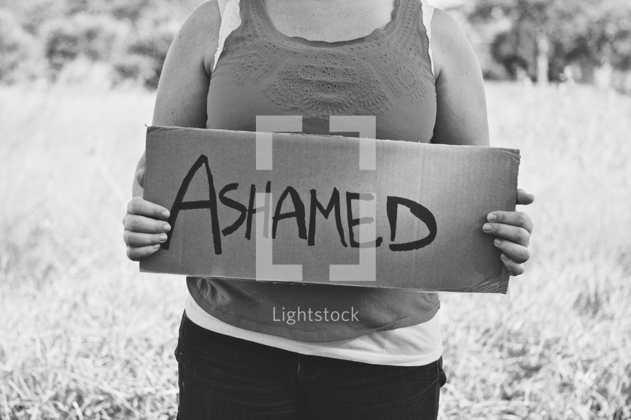 woman holding a sign that reads ASHAMED