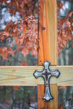 A decorative cross nailed to a large wooden cross.