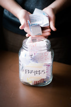 "A child putting hand written notes into a jar labeled ""prayers."""