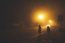men walking down a dark street