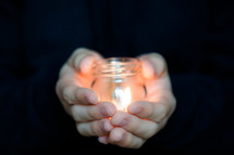 Hands holding a burning candle in a jar.