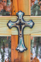 A decorative ceramic cross attached to a larger wooden cross.