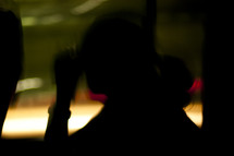 A silhouette of a woman staring out the window