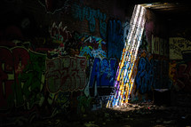 rays of sunlight shining on a graffiti covered wall