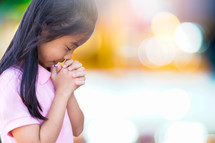 a girl with head bowed praying
