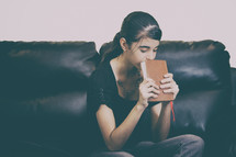 a teen girl sitting on a couch holding a Bible and praying
