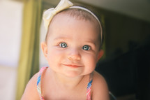 Smiling baby with a bow in her hair.
