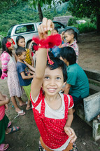 a little girl holding a hibiscus flower