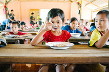 children in an orphanage eating in a cafeteria