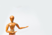 Wooden figure pose raising arm hand to introduce product for business