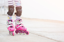 a girl roller blading with knee pads