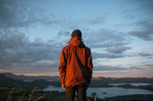 a man in a jacket looking out at mountains