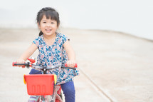 a little girl learning to ride a bicycle
