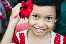 a little girl with a hibiscus flower behind her ear