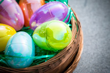Multi-colored plastic Easter eggs in a circular brown basket