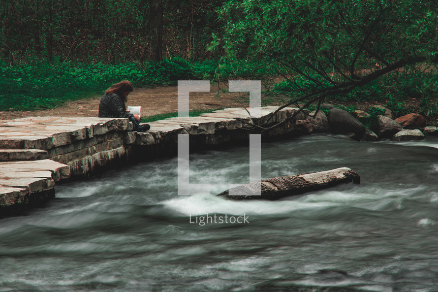 a woman sitting on rocks next to a fast flowing river