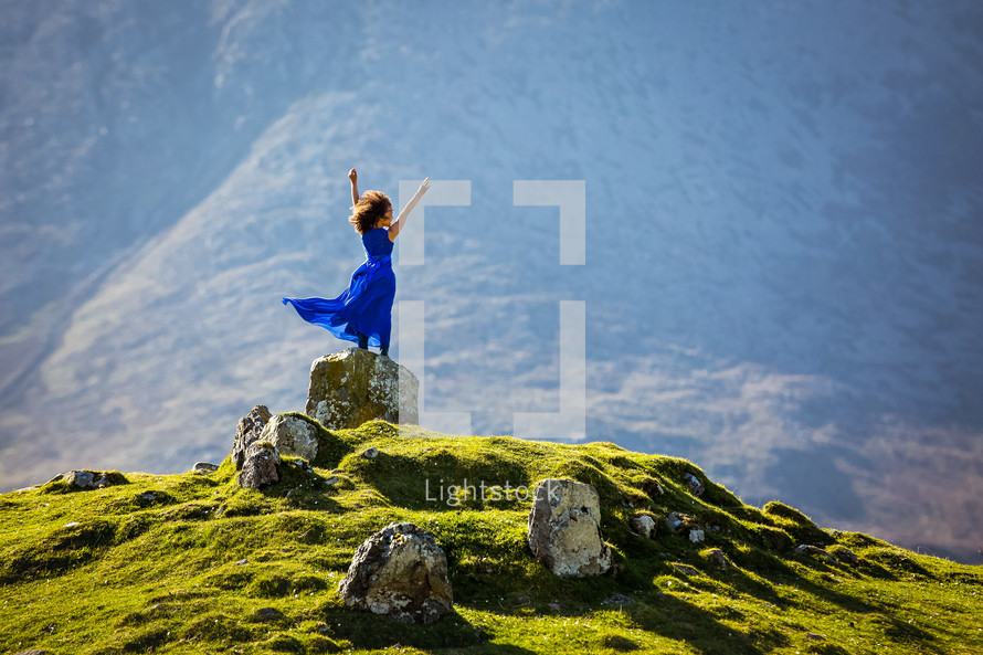 a girl in a blue dress standing on a rock on a green mountain with arms raised
