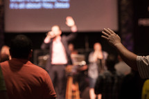 a preacher giving a sermon and raised hands at a worship service