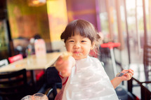 girl with a bib eating food
