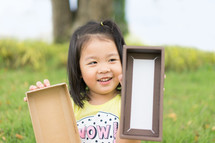 a toddler girl holding an empty box