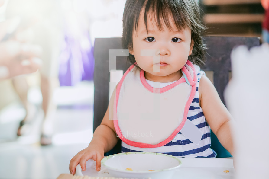 toddler in a bib in a highchair