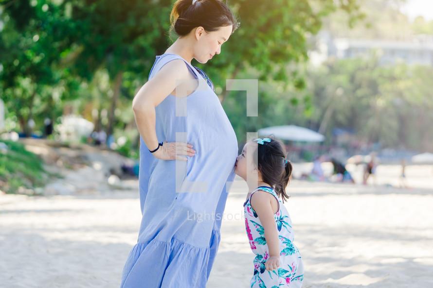 toddler girl kissing mom's pregnant belly