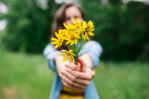 a woman holding yellow flowers