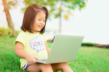 a toddler sitting in grass with a laptop on her lap