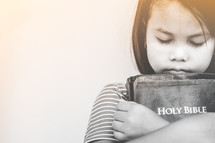girl hugging a Bible