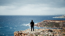 a man standing on a rugged shore