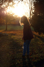 a woman standing in a park at sunset