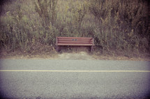 Wooden bench on the side of the road.