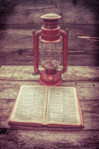 lantern and open Bible on wood boards