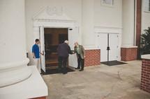 greeters welcoming parishioners at church doors