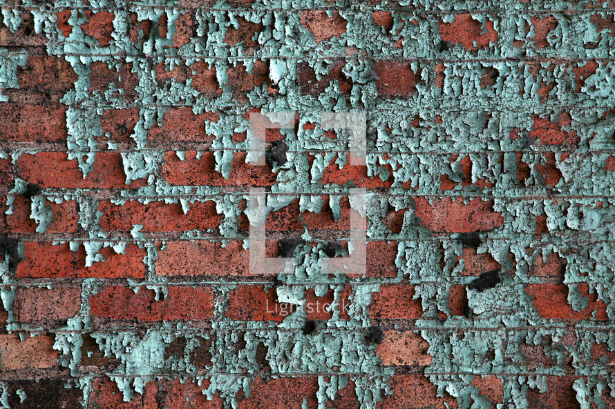 Green paint peeling from red bricks.