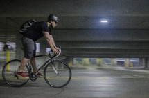 a man riding a bicycle in a parking garage