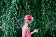 A little blonde girl walks along a wall with hanging green vines.