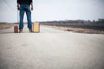man looking down a road standing next to suitcases