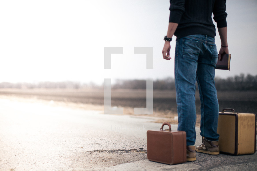 man standing next to a suitcase holding a Bible looking down a road wondering where to go from here