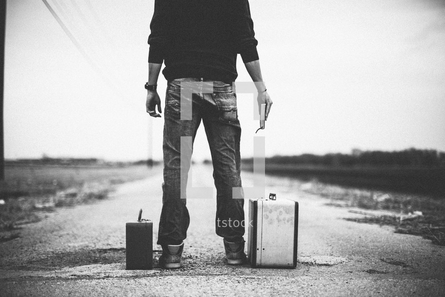 man standing next to suitcases looking down a road holding a Bible