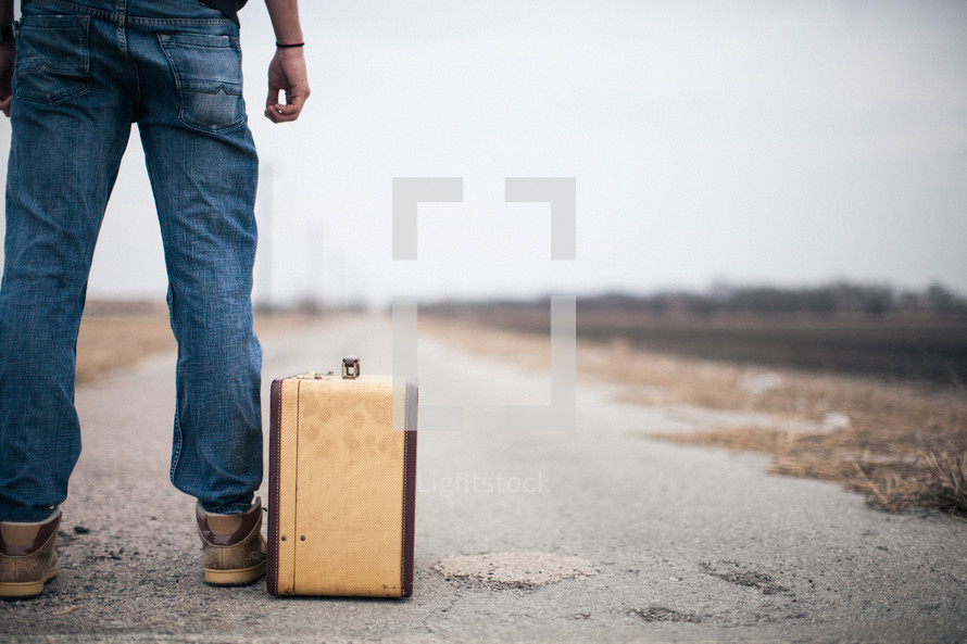 man looking down a road standing next to a suitcase