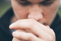 close-up of a man with his hand held in prayer