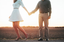 a couple holding hands standing on a rural road