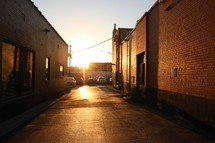 warm sunlight hitting the pavement in an alley