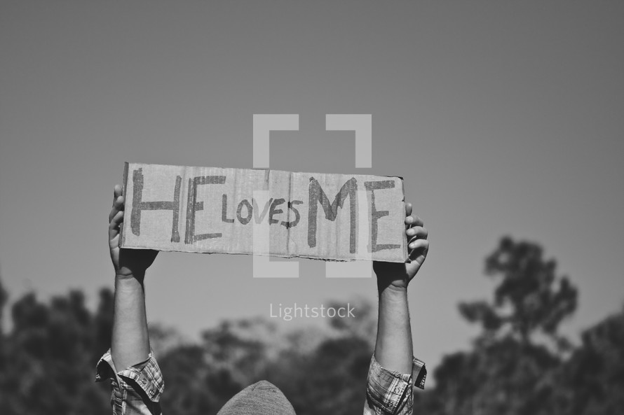 "Boy holding ""He Loves Me"" sign"