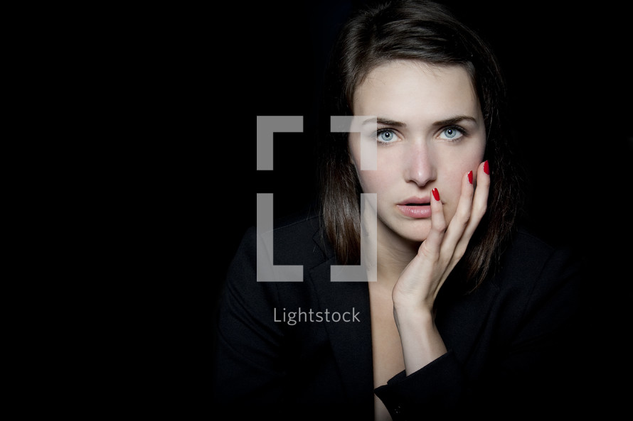 In the Darkness - woman with her hand on her cheek