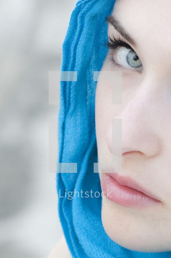 Lady Macbeth; woman with blue scarf looking toward camera.